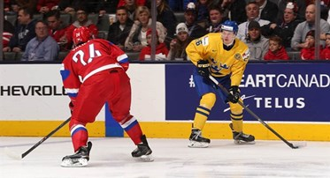 TORONTO, CANADA - JANUARY 4: Sweden's Christoffer Ehn #26 skates with the puck while Russia's Rinat Valiev #24 defends during semifinal action at the 2015 IIHF World Junior Championship. (Photo by Andre Ringuette/HHOF-IIHF Images)